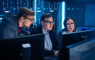 Managed IT team of three IT professionals monitors networks from a server room.